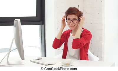 Young beautiful woman sitting at table in office.