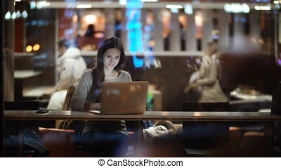 Young beautiful woman sitting at the table and using the laptop. View inside the window on female working in cafe.