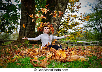 Young beautiful woman sitting by maple tree with yellow leaves in fall