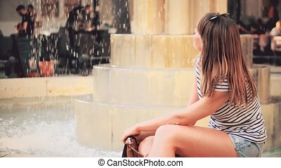 Young beautiful woman sitting by the fountain