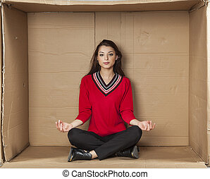 Young beautiful woman sitting in a cardboard box office