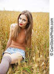 Young beautiful woman sitting in a field