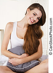 Young beautiful woman sitting in bed