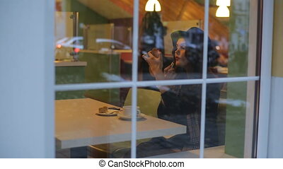 Young beautiful woman sitting in cafe and lipstick