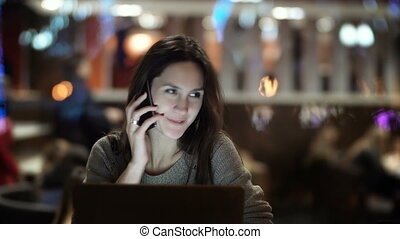 Young beautiful woman sitting in cafe and talking on the phone. Brunette female working on laptop computer in evening.