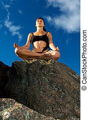 beautiful woman sitting in lotus pose on the beach
