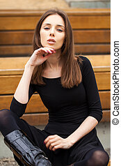 Young beautiful woman sitting on a bench