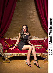 Young beautiful woman sitting on a red velvet sofa in the interior in gold