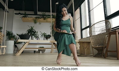Young beautiful woman sitting on a swing and making recordings in her notebook