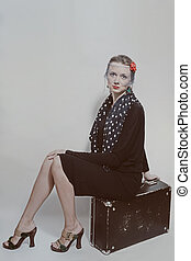 Young beautiful woman sitting on an old suitcase