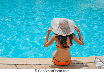 Young beautiful woman sitting on edge of the pool