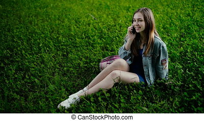 Young beautiful woman sitting on grass in summer city park and talking on cell phone.