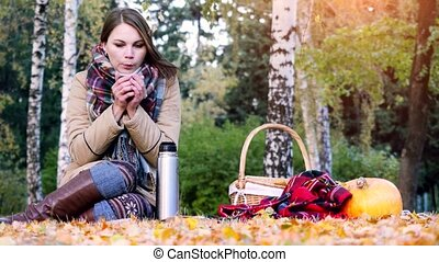 Young beautiful woman sitting on picnic drinking hot tea...