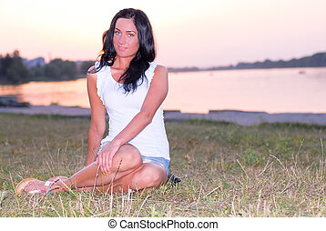 Young beautiful woman sitting on river bank at sunset