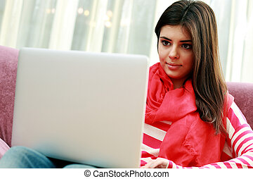Young beautiful woman sitting on the sofa and using laptop at home