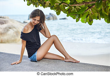 Young beautiful woman sitting on the tropical beach