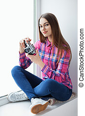 Young beautiful woman sitting on window sill with old film camera