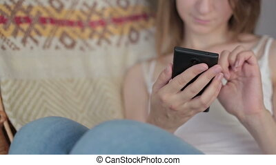 Young beautiful woman sitting with smart phone.