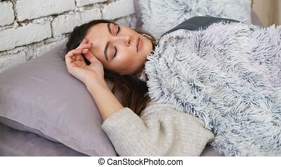 Young beautiful woman sleeping in her bed relaxing at home