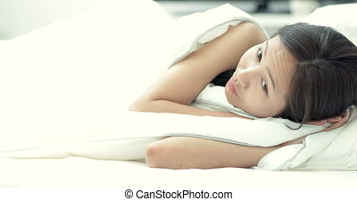 Young beautiful woman sleeping on bed in bedroom And looking camera with smile face .