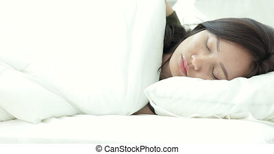 Young beautiful woman sleeping on bed in bedroom .