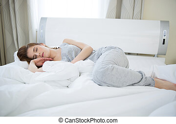 Young beautiful woman sleeping on the bed at home