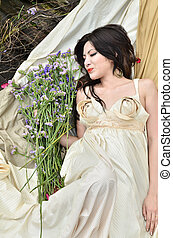 Young beautiful woman sleeping with flowers outdoor