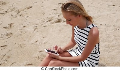 Young beautiful woman slim with long blond hair in black and white dress is sitting on the beach and using a smartphone. Girl on the beach touching the screen.