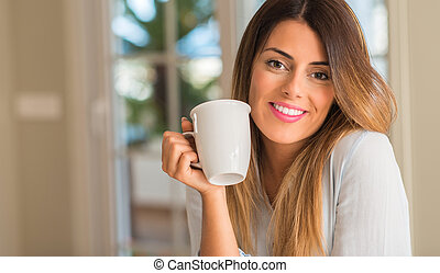 Young beautiful woman smiling holding a cup of coffee at home