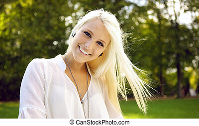 Young beautiful woman smiling on a sunny day - Portrait shot...