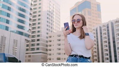 Young beautiful woman smiling with smartphone in hand...