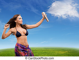 Young beautiful woman sprays clouds on a sunny day