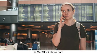 Young beautiful woman standing at the airport calling on the...