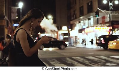 Young beautiful woman standing in downtown, near the...