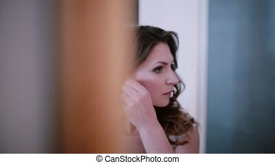 Young beautiful woman standing in front of mirror, looking at reflection and putting on the ear rings.