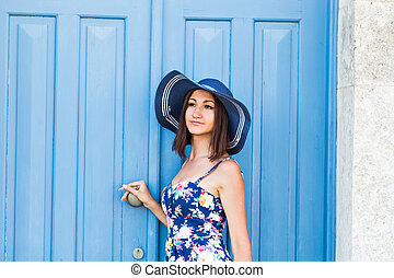 Young beautiful woman standing in front of a blue vintage entrance door