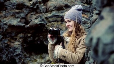 Young beautiful woman standing in the mountains and filming...