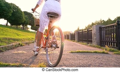 Young beautiful woman standing near her bicycle at sunset. Slow motion