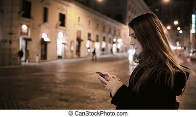 Young beautiful woman standing near the traffic road in downtown in evening and using the smartphone.