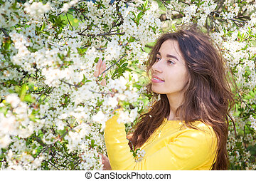 young beautiful woman standing near tree with flowers