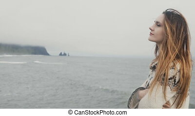 Young beautiful woman standing on the black beach, smiling...