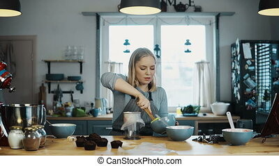 Young beautiful woman standing on the kitchen and cooking cupcakes. Blonde female puts the cream in pastry bag.