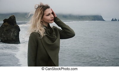 Young beautiful woman standing on the shore of the sea alone...