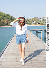 young beautiful woman standing on wood pier with blue sea water