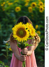 Young beautiful woman stands in a field of sunflowers,...