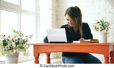 Young beautiful woman student sitting with laptop and writing book at cafe indoors