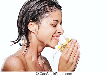 Young beautiful woman taking a shower and holding exotic flowers. Isolated over white background.