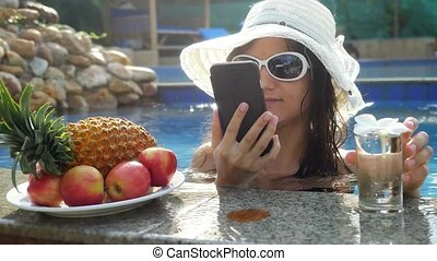 Young beautiful woman talking and uses mobile phone in swimming pool next to the glasses of the water and plate with tropical fruits.