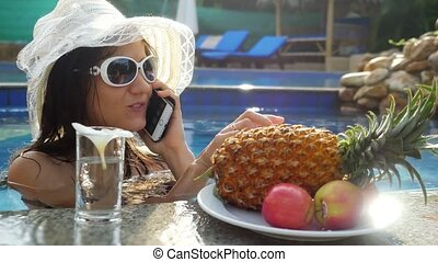 Young beautiful woman talking on mobile phone eats apple in swimming pool next to the glasses of the water and plate with tropical fruits. 3840x2160, 4k