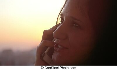 Young beautiful  woman talking on the phone at silhouette of city sunset